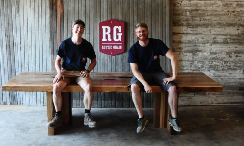 Barnwood furniture builders and designers Matthew and Tim sitting on conference table with Rustic Grain logo in the background.