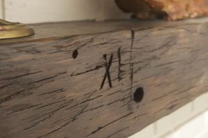 A close up of the Moore mantel focusing on the XI found carved in the original beam.