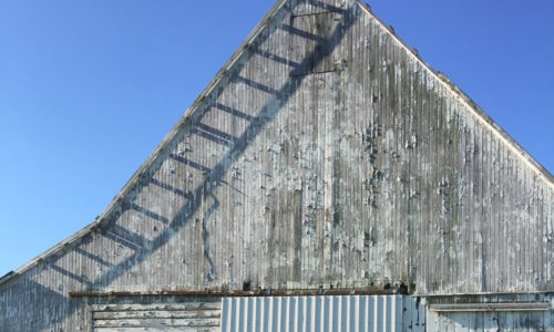 Weathered Grey Barn against a clear blue sky