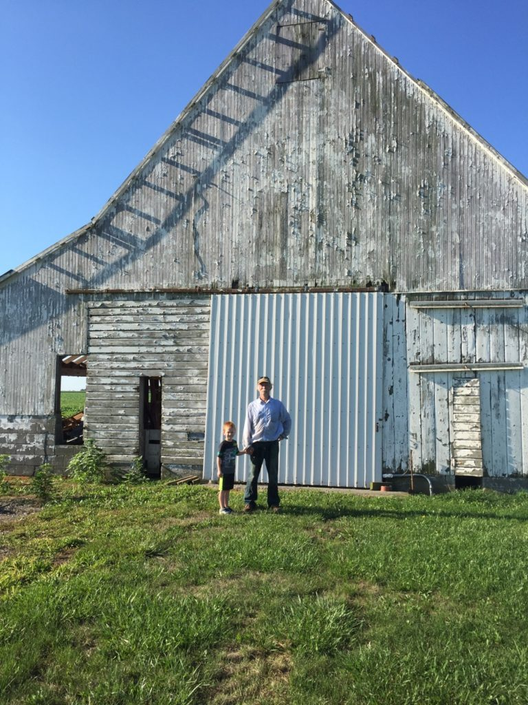 Fullshot of weathered grey barn; Grandfather and son in foreground