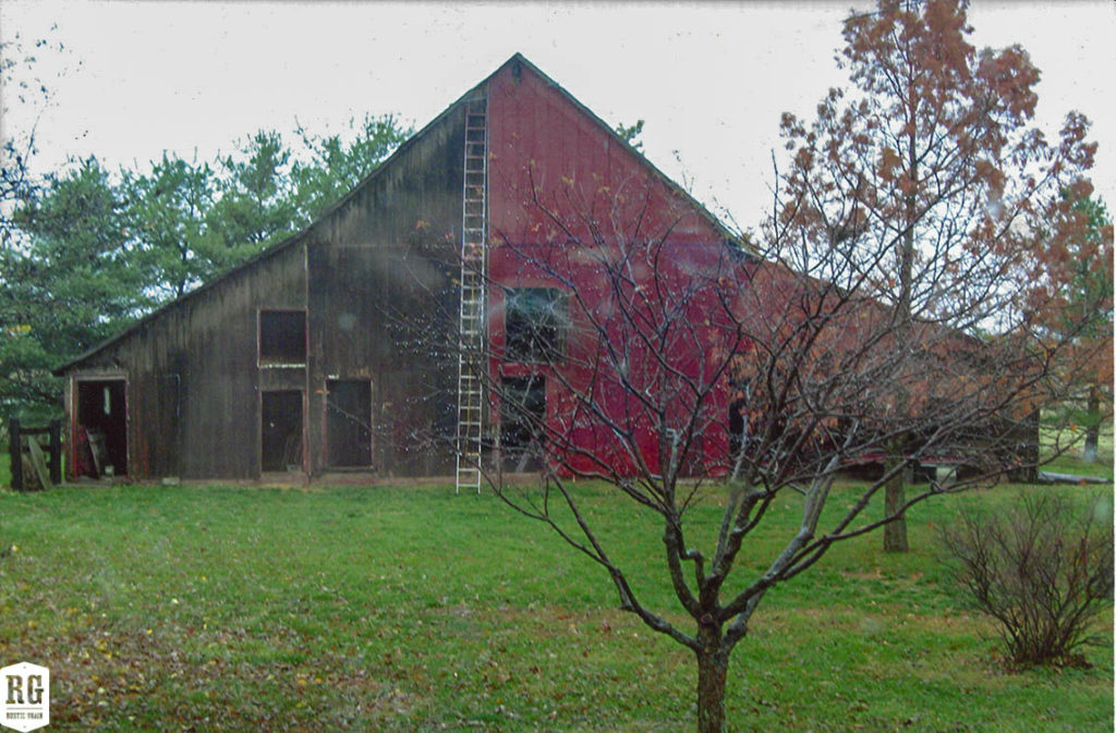 Brown and red barn with peaked roof. A tree with autumn leaves in the foreground.